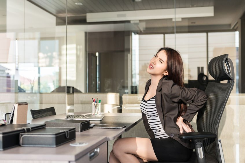 39343210 - young businesswoman having back pain while sitting at office desk